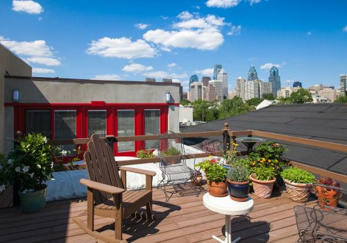 A Fitler Square roof deck designed with a glass paneled pilot house and a skyline view