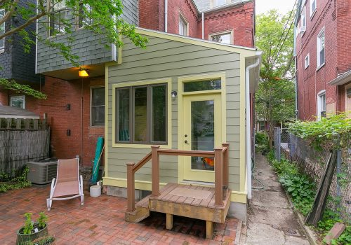 A Small addition in Philadelphia design-build with a laundry room, exposed brick and patio