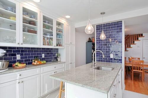 Compact kitchen, bath, and office addition including a peninsula counter and blue accents
