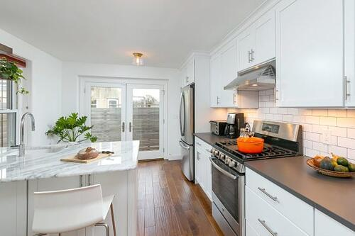 Classic white kitchen featuring design-build salvaged architectural elements