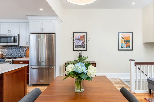 Quaint dining room and kitchen remodel with brown wooden table and blue chairs by Bellweather Design-Build in Philly