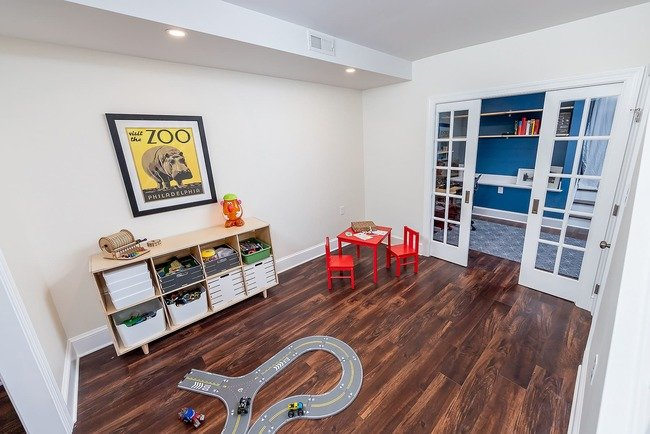 Children's basement playroom with hardwood floors and toy car track by Bellweather Design-Build in Philadelphia