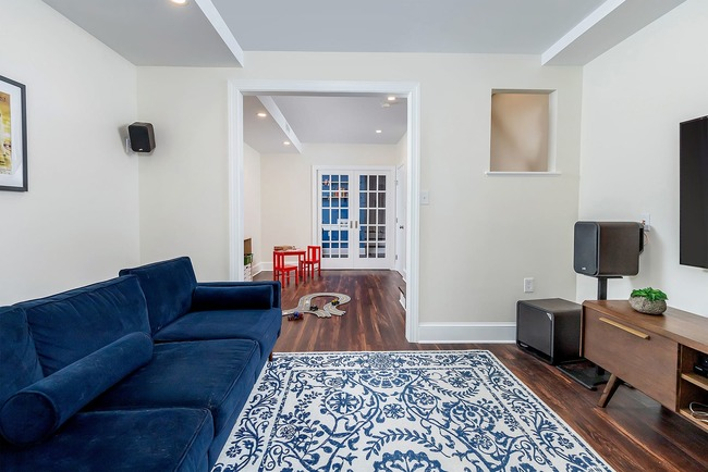 Modern basement remodel with dark hardwood floors and blue couch by Bellweather Design-Build in Philly