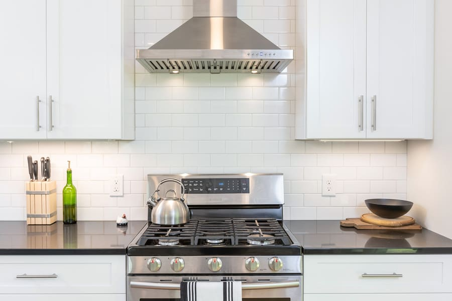 White kitchen with stainless steel stove hood and oven by Bellweather Design-Build in Mount Airy