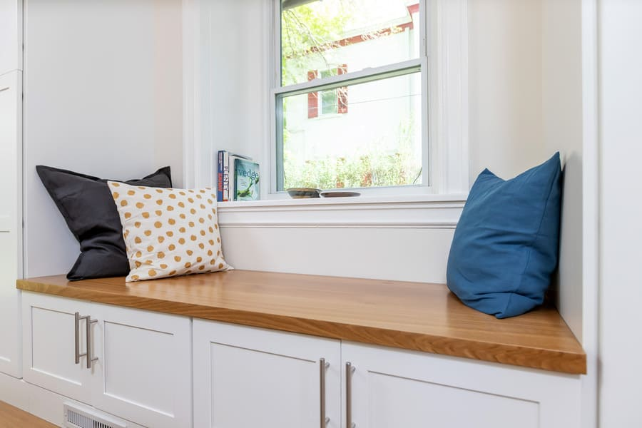 Kitchen window bench with blue, black, and polka dot pillows by window overlooking outdoors by Bellweather Design-Build