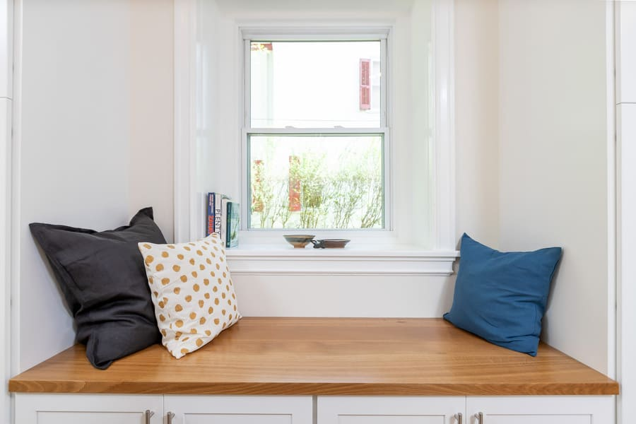 Wood reading bench near white window in transitional Mount Airy kitchen by Bellweather Design-Build