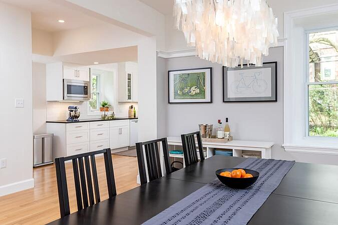 Black dining room table with blue runner and oranges on table in transitional kitchen by Bellweather Design-Build in Philadelphia