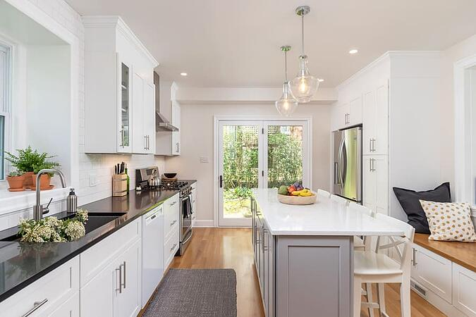 Remodeled Mount Airy transitional kitchen with large island and seated window bench by Bellweather Design-Build