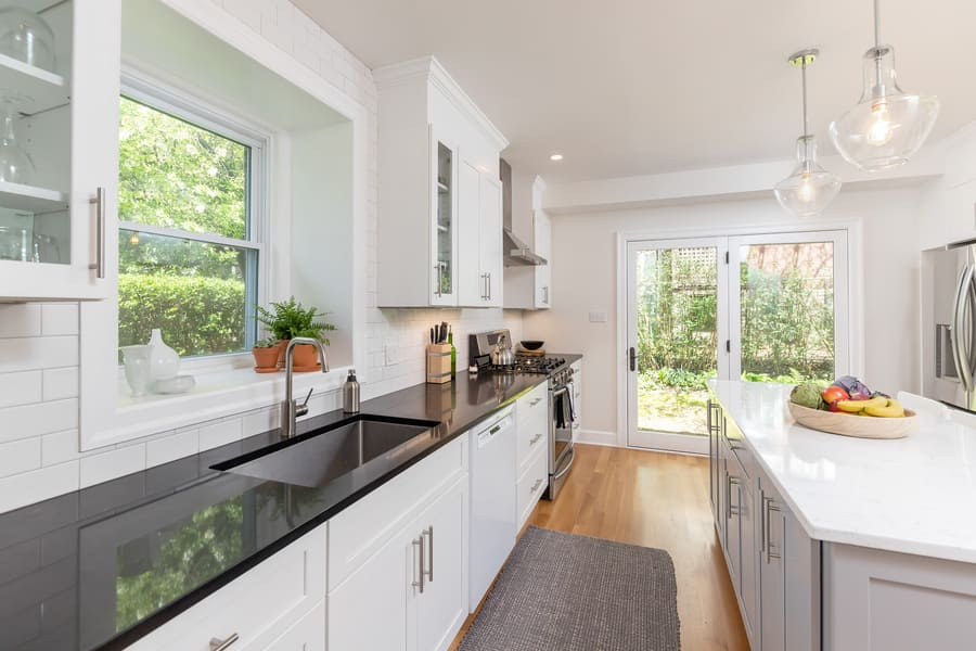 Black and white transitional kitchen remodel by Bellweather Design-Build with black countertops, white island, and stainless steel appliances