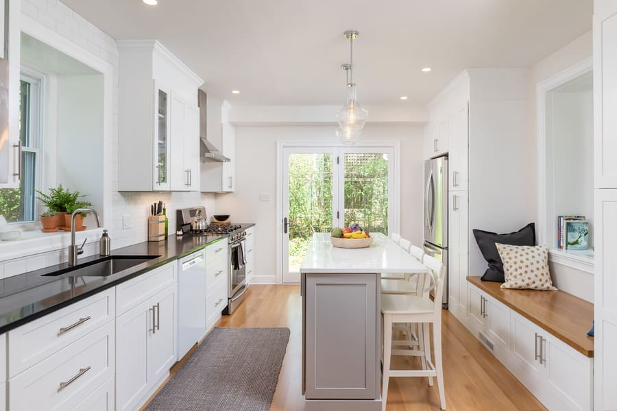 Full view of Mount Airy transitional kitchen with stainless steel appliances, black countertops, white kitchen island, and wood reading bench near window by Bellweather Design-Build