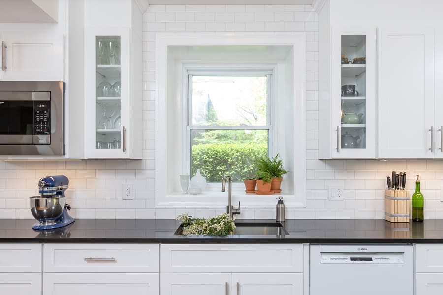 Transitional kitchen with black countertops and stainless steel sink with flowers inside by Bellweather Design-Build in Mount Airy