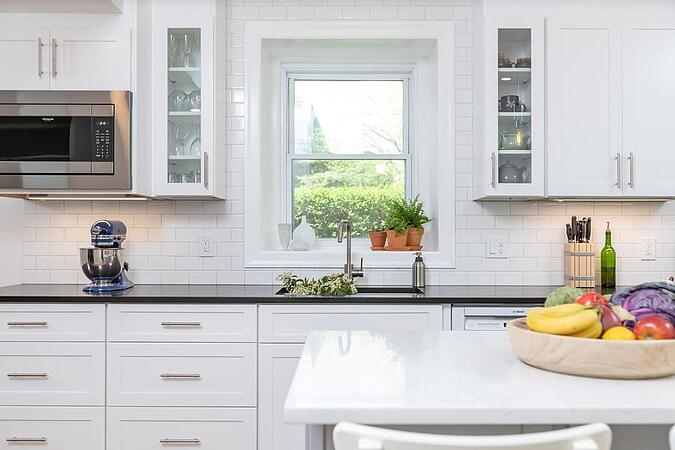 Bright Mount Airy transitional kitchen remodel with black countertops and white cabinets and island by Bellweather Design-Build