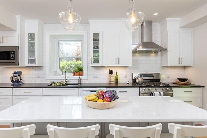 White kitchen island with bowl of fruit and four bar chairs by Bellweather Design-Build in Philadelphia