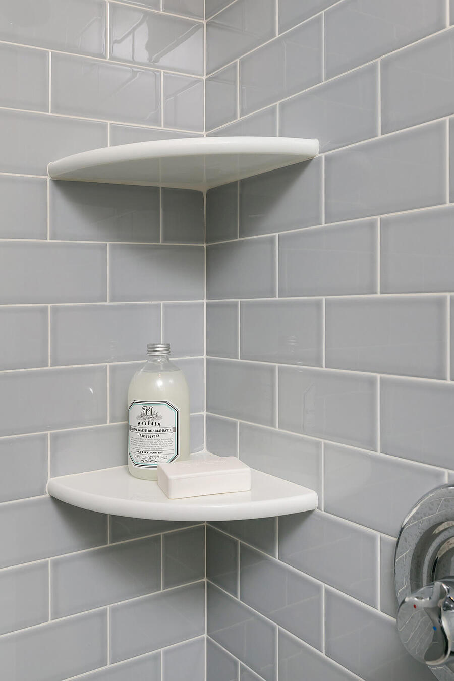 Two Shelves in Shower with Shower Products on Them