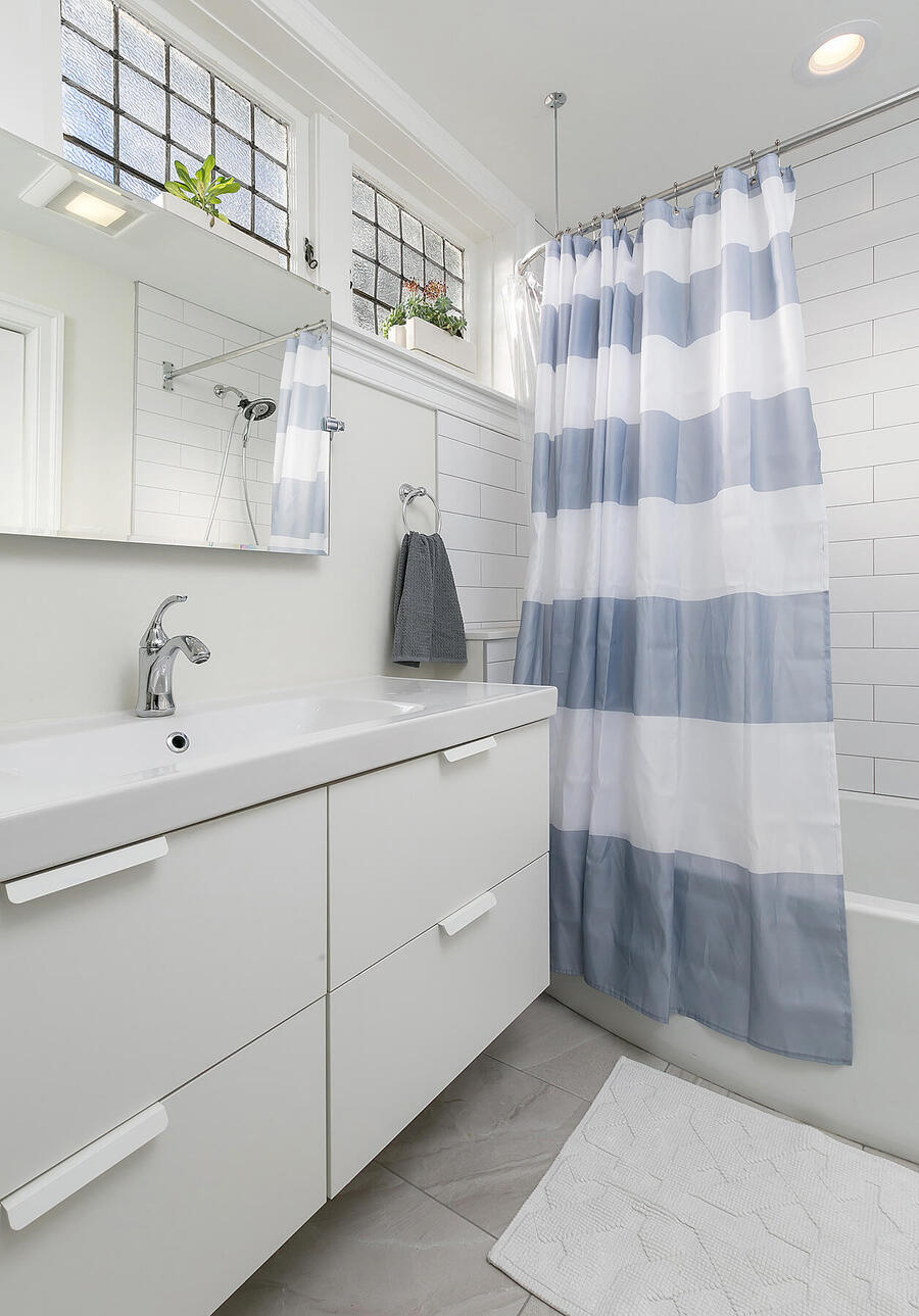 Sink with Striped Shower Curtain Next to It