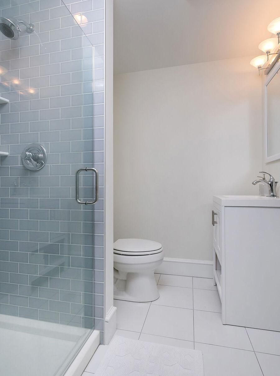 Small Toilet Next to Gray Brick Shower