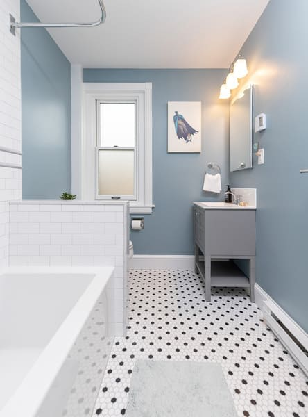 A Wonderful Grey Accented Bathroom Featuring Black and White Tile and Grey Sink
