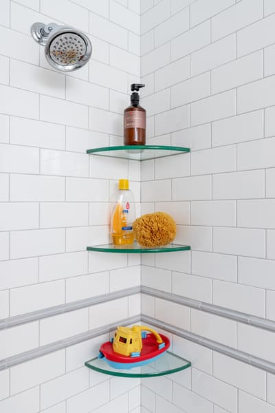White Brick Shower Featuring Some Shampoo on Glass Shelves