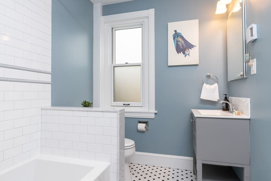 A Wonderful Grey Accented Bathroom Featuring Black and White Tile and Grey Sink With a Large Tub