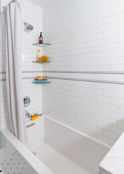 White Brick Shower Featuring Some Shampoo on Glass Shelves and a Large Tub
