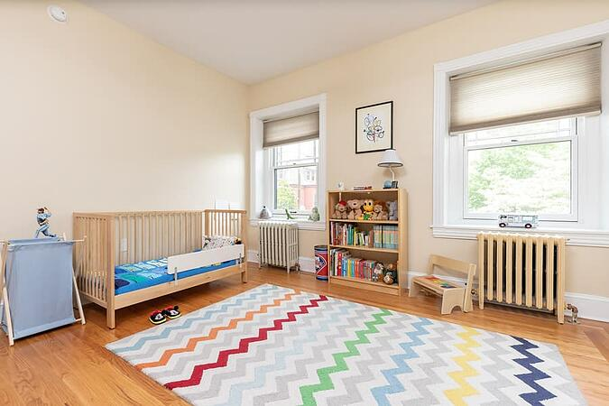 Playful kids room with wooden crib and floors with patterned rug and bookshelf by Bellweather Design-Build in Philadelphia