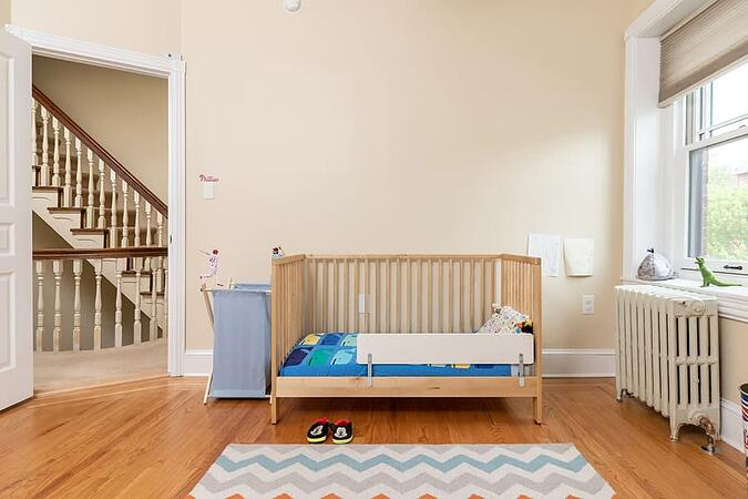 Light wooden crib with blue bed sheets in new traditional kitds room by Bellweather Design-Build in Philly