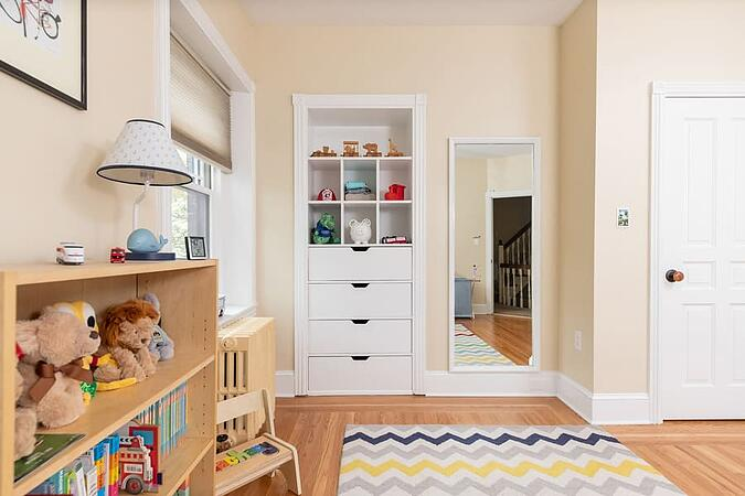 Traditional style kids room with beige walls and built-in shelving by Bellweather Design-Build in University City