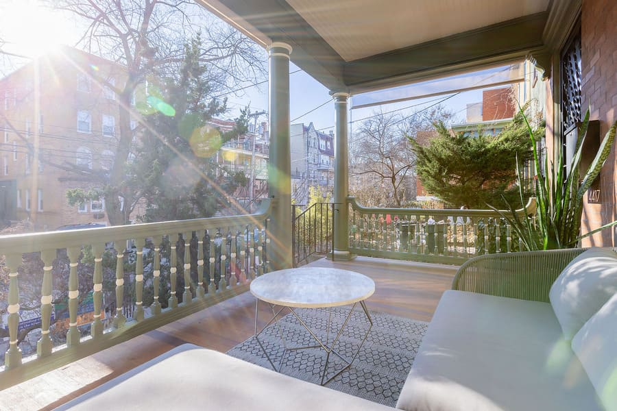 Sun-filled historic porch renovation in Squirrel Hill with spacious seating area and green railing by Bellweather Design-Build