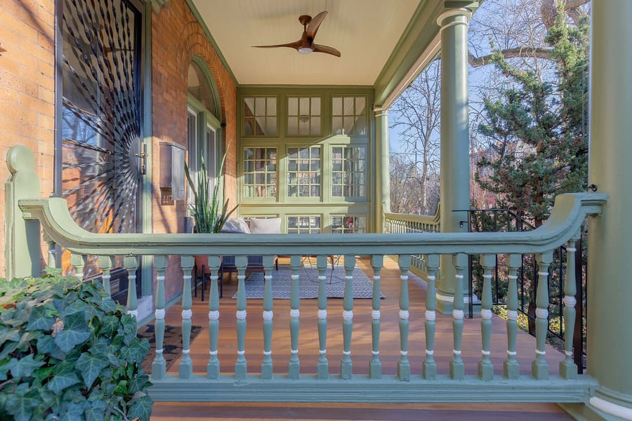Victorian-style porch restoration in Squirrel Hill with green railing and honey-colored hardwood decking by Bellweather Design-Build