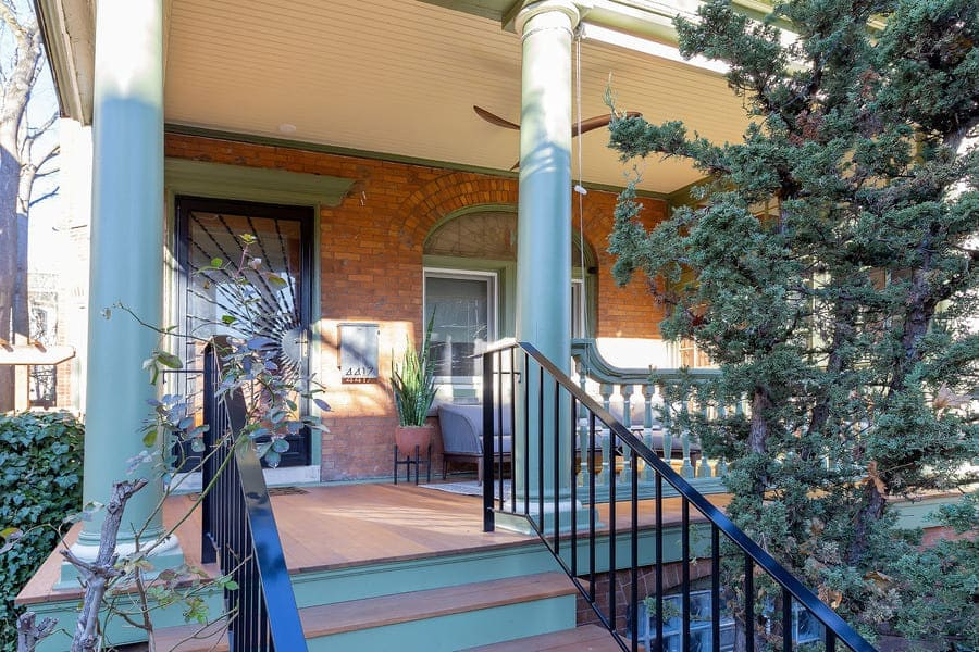 Colorful Victorian porch restoration in Squirrel Hill, PA, with black railing and green painted stairs by Bellweather Design-Build