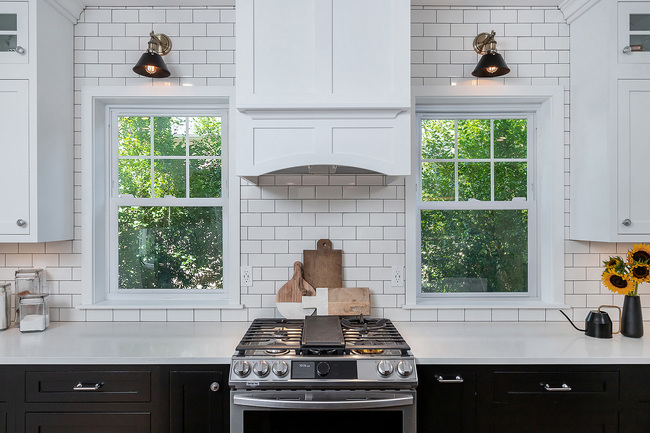 Stainless Steel Stove Between White Counter and Two Windows