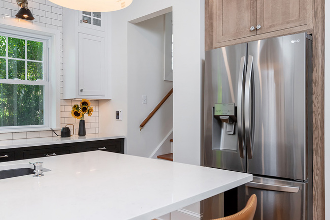 White Kitchen Counter with Stainless Steel Fridge