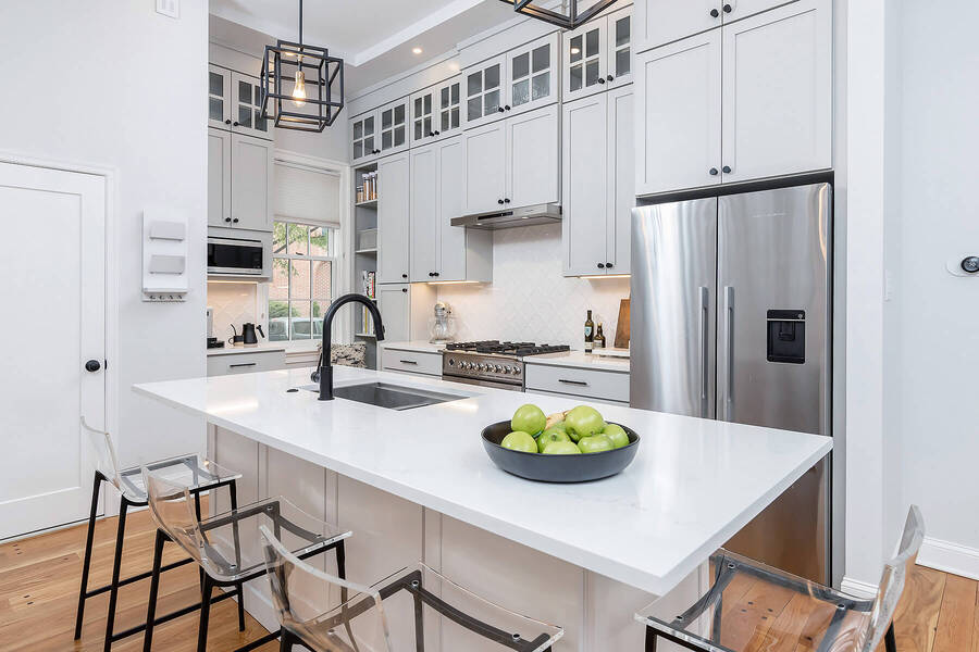 Beautiful white kitchen island with built-in sink by Bellweather Design-Build in Philly