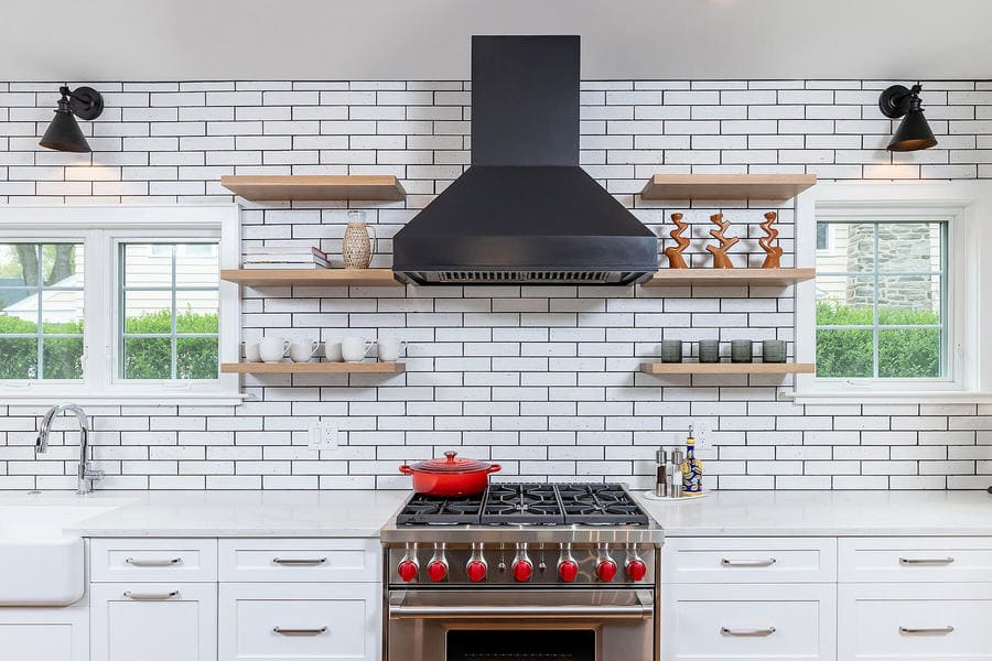 Farmhouse brick style kitchen remodel with metal stove with red knobs by Bellweather Design-Build in the Main Line
