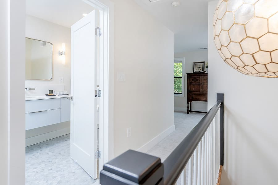 Long hallway with cream walls leading to white transitional bathroom by Bellweather Design-Build in Philadelphia