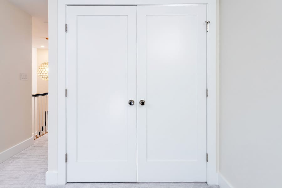Closed white closet doors with hidden washer and dryer inside by Bellweather Design-Build in Philly