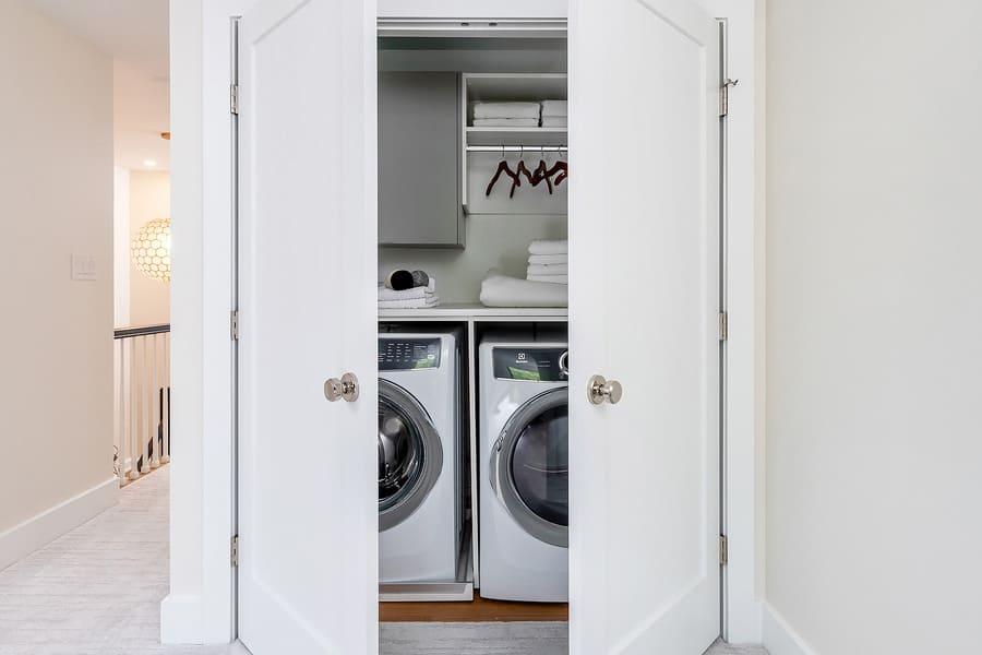 Hidden white washer and dryer in closet in hallway by Bellweather Design-Build in Philadelphia