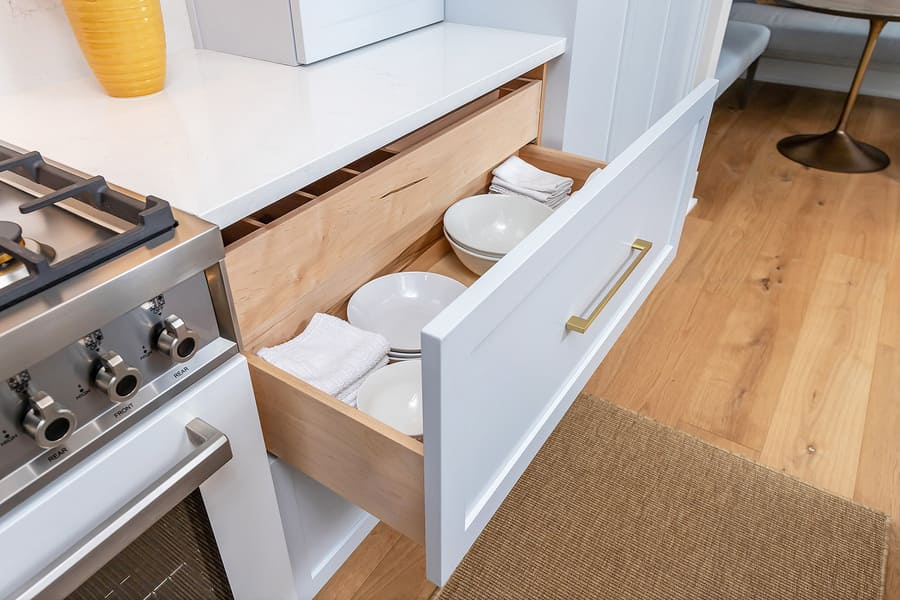 Drawer filled with white plates and bowl in transitional kitchen by Bellweather Design-Build in Philly