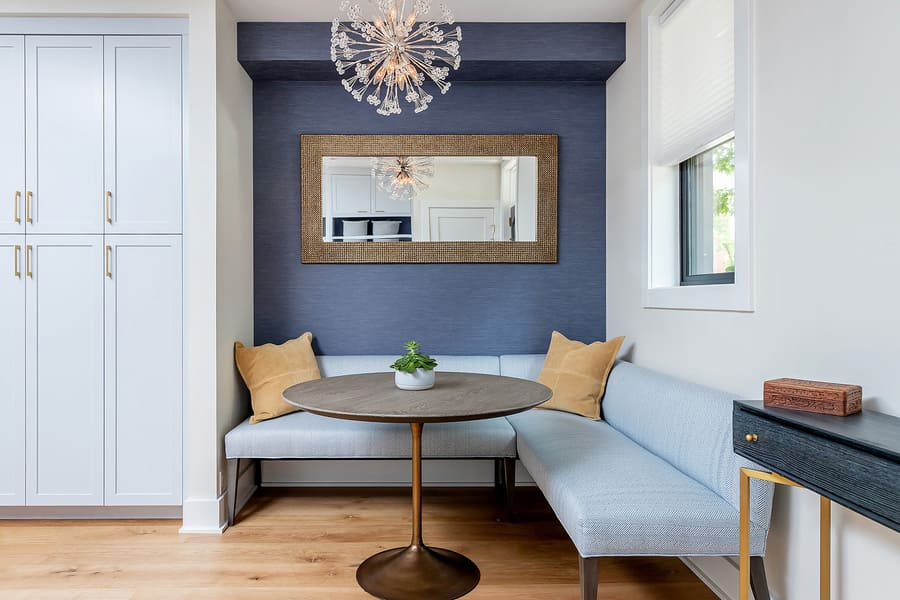 Grey and yellow breakfast nook booth with small round table and wide mirror above seating by Bellweather Design-Build in Philadelphia