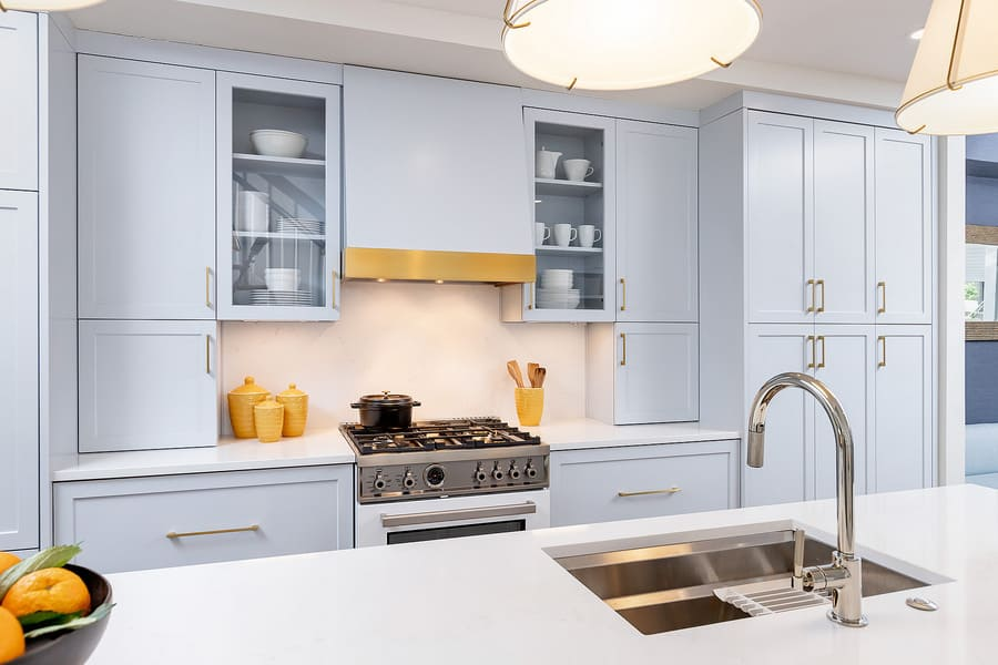 White cabinets and black stove with stainless steel sink in white kitchen island by Bellweather Design-Build in Philadelphia