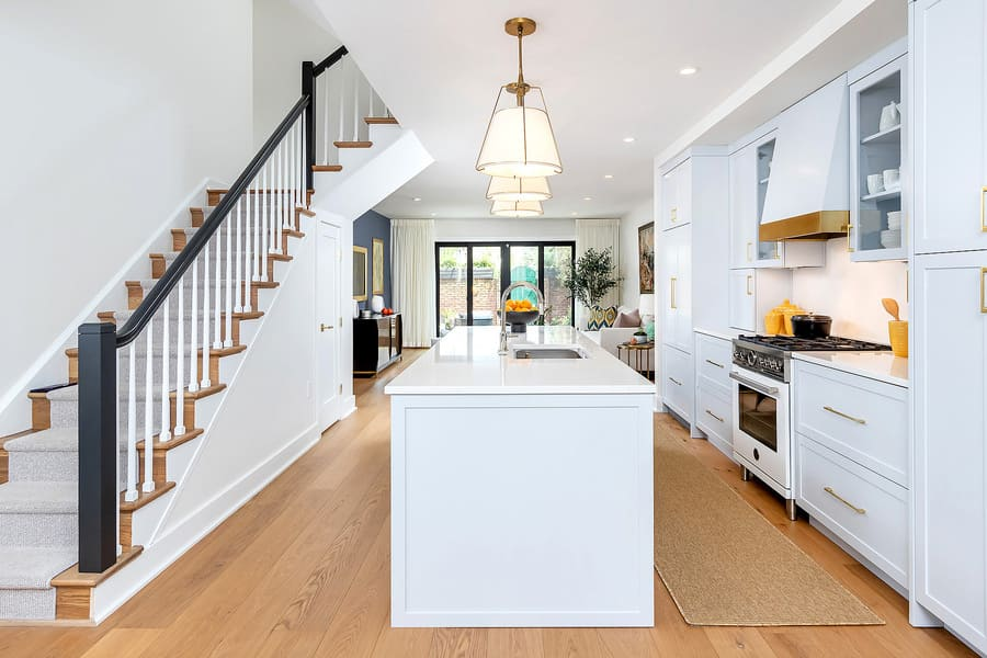 Philadelphia transitional white kitchen with staircase to left and island in middle by Bellweather Design-Build