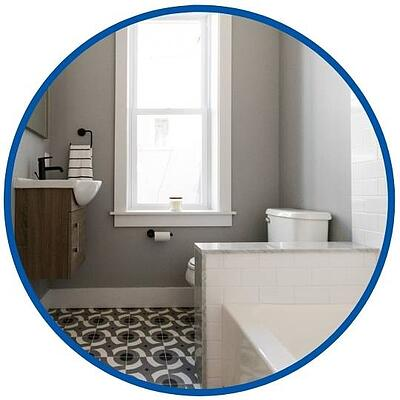 photo of grey bathroom with white bathtub and black sink faucet by Bellweather Design Build in Philadelphia